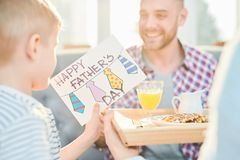 Handmade Fathers Day Card. Warm toned shot of little boy giving his dad handmade Fathers day card and surprise breakfast at home, copy space stock image