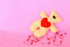 Handmade felt bear. Beige felt bear on pink background, hand-stitched toy, a craft out of felt Stock Images