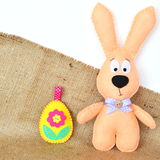 Handmade felt beige rabbit and an Easter egg on burlap and white background. Easter crafts for kids Royalty Free Stock Photos