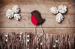 Handmade from felt bird robin on wooden background. Craft arranged from sticks, twigs, driftwood and pine cones white and shiny. Royalty Free Stock Image