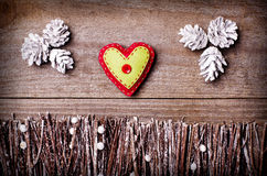 Handmade from felt heart on wooden background. Craft arranged from sticks, twigs, driftwood and pine cones white and shiny Royalty Free Stock Photography