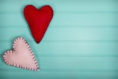 Handmade felt hearts turquoise background Stock Images