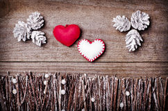 Handmade from felt hearts on wooden background. Craft arranged from sticks, twigs, driftwood and pine cones white and shiny. Stock Image