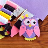 Handmade felt owl toy, felt sheets, scissors, thread, pins, needle on a brown wooden background. Sewing concept Royalty Free Stock Photos