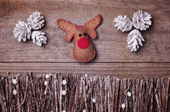Handmade from felt Rudolph reindeer on wooden background. Craft Royalty Free Stock Photo