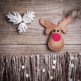 Handmade from felt Rudolph reindeer on wooden background. Craft Royalty Free Stock Images