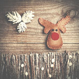 Handmade from felt Rudolph reindeer on wooden background. Craft Stock Image