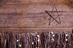 Handmade from felt star on wooden background. Craft arranged from sticks, twigs, driftwood and pine cones white and shiny Royalty Free Stock Photography
