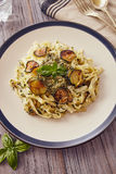 Handmade fettuccine pasta. With pesto genovese sauce and fried courgette Royalty Free Stock Images