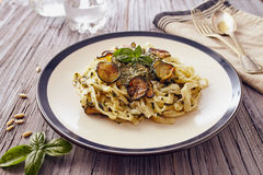 Handmade fettuccine pasta. With pesto genovese sauce and fried courgette on white dish with a blue border, on a wooden table Stock Images