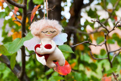 Handmade figure of Angel hanging in autumn garden. Royalty Free Stock Photography