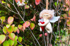 Handmade figure of Angel hanging in autumn garden. Royalty Free Stock Image