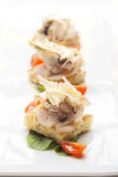 Crostini di focaccia, Italian Fine Dining Appetizer. Handmade Focaccia Bread topped with ham, pioppini mushrooms and Parmigiano Cheese Royalty Free Stock Image