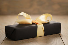 Handmade gift black paper box with yellow ribbon bow on wood table. Closeup photo stock photography