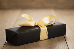 Handmade gift black paper box with yellow ribbon bow on wood table. Closeup photo stock images
