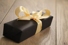 Handmade gift black paper box with yellow ribbon bow on wood table. Closeup photo with shallow focus stock photo