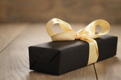 Handmade gift black paper box with yellow ribbon bow on wood table. Closeup photo with shallow focus stock image