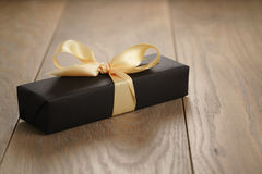 Handmade gift black paper box with yellow ribbon bow on wood table. Closeup photo with shallow focus royalty free stock photography