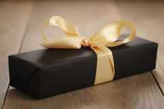Handmade gift black paper box with yellow ribbon bow on wood table. Closeup photo with shallow focus royalty free stock image