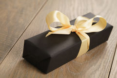 Handmade gift black paper box with yellow ribbon bow on wood table. Closeup photo with shallow focus royalty free stock photos