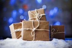 Handmade gift boxes from craft paper over snowy wooden table in blue light. Stock Photos