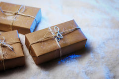 Handmade gift boxes from craft paper over snowy wooden table in blue light. Stock Images