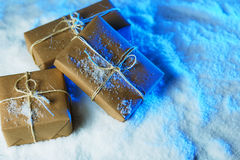 Handmade gift boxes from craft paper over snowy wooden table in blue light. Royalty Free Stock Images