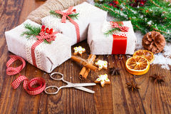 Handmade gift boxes near Christmas tree with cookies and spices. Royalty Free Stock Photography