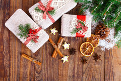 Handmade gift boxes near Christmas tree with cookies and spices. Stock Images