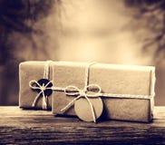 Handmade gift boxes in sepia tone. Handmade gift boxes on wooden board in sepia tone Royalty Free Stock Photography