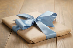 Handmade gift brown paper box with blue ribbon bow on wood table Stock Photo