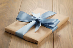 Handmade gift brown paper box with blue ribbon bow on wood table Royalty Free Stock Photo