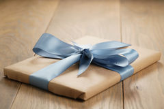 Handmade gift brown paper box with blue ribbon bow on wood table Royalty Free Stock Photos