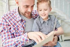 Handmade Gift for Fathers Day. Cheerful little boy and his handsome young dad wrapped up in reading Fathers Day greeting card while gathered together at cozy stock images