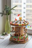 A gingerbread carousel and some Christmas decoration elements on a white wooden surface. A handmade gingerbread carousel and some Christmas decoration elements Royalty Free Stock Photos