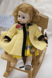 Handmade Girl Doll on Rocking Chair. Handmade Girl Doll with yellow and black clothing sitting on Rocking Chair stock photography