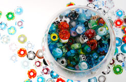 Handmade glass beads in bowl. Colorful glass beads in a glass bowl and white surface Royalty Free Stock Photography