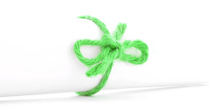 Handmade green string bow tied on white paper roll  Royalty Free Stock Photo