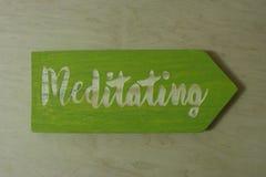 Yoga class sign. Handmade green wooden `Meditating` sign royalty free stock image