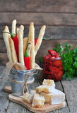Handmade Grissini, parmesan cheese, salami, parsley and dried tomatoes on wood background Stock Photos