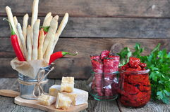 Handmade Grissini, parmesan cheese, salami, parsley and dried tomatoes on wood background Royalty Free Stock Photo