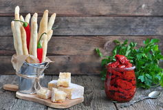 Handmade Grissini, parmesan cheese, salami, parsley and dried tomatoes on wood background Royalty Free Stock Photography