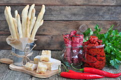 Handmade Grissini, parmesan cheese, salami, parsley and dried tomatoes on wood background Stock Photo