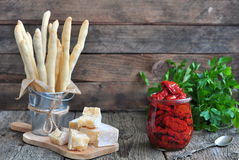 Handmade Grissini, parmesan cheese, salami, parsley and dried tomatoes on wood background Royalty Free Stock Photos