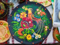 Handmade and handpainted decorative ceramic plate, bright floral patterns and fantastic bird, Petrykivka painting style. Handmade and handpainted decorative stock photography