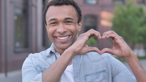 Handmade heart by african man standing outdoor stock footage