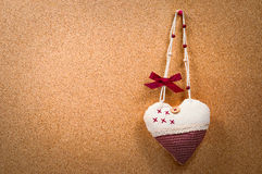 Handmade heart cloth hanging on the side of a cork board symbol romance valentines Royalty Free Stock Image