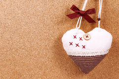 Handmade heart cloth hanging on the side of a cork board symbol romance valentines.  Royalty Free Stock Photos