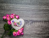 Handmade heart shape box with decoration bouquet of roses on grey wooden background stock photography