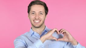Handmade Heart by Young Man Isolated on Pink Background